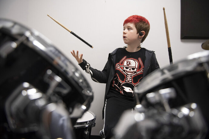 In a Thursday, October 30, 2019 photo, Cade Suddith, 10, flips a drum stick during a practice at Jim's House of Music in New Market, Maryland. (Graham Cullen/The Frederick News-Post via AP)
