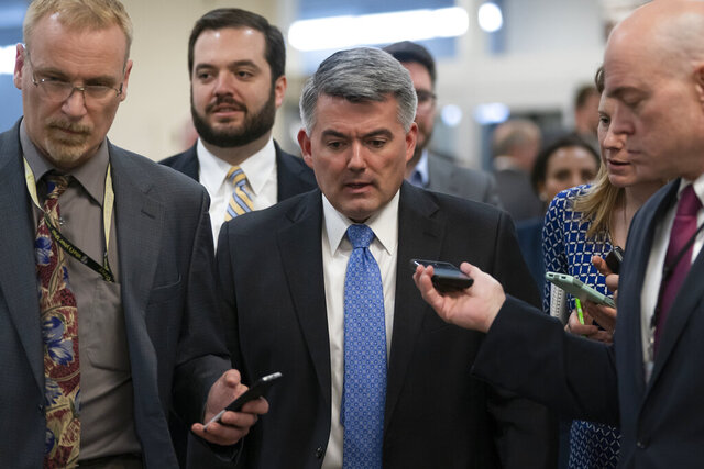 FILE - In this March 13, 2019 file photo, reporters pose questions to Sen. Cory Gardner, R-Colo., on his way to a vote at the Capitol in Washington. (AP Photo/J. Scott Applewhite)