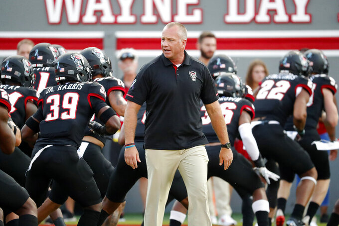 FILE - North Carolina State head coach Dave Doeren watches his team warm up prior to the start of an NCAA college football game against Ball State in Raleigh, N.C., Saturday, Sept. 21, 2019. Doeren said the team had three positive coronavirus tests over 2½ months before students returned. Clusters followed and the school soon paused all athletics activities, including football practices for about a week before postponing this weekend's game at Virginia Tech to Sept. 26.  (AP Photo/Karl B DeBlaker, File)