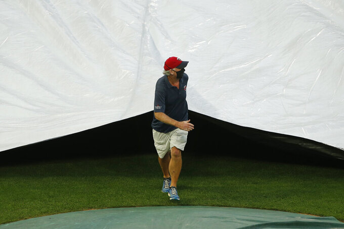 Minnesota Twins head grounds keeper Larry Devito pulls a tarp across the infield prior to the postponement of a baseball game with the Kansas City Royals, Friday, Aug. 14, 2020, in Minneapolis. The game was postponed due to multiple approaching thunderstorms. (AP Photo/Bruce Kluckhohn)