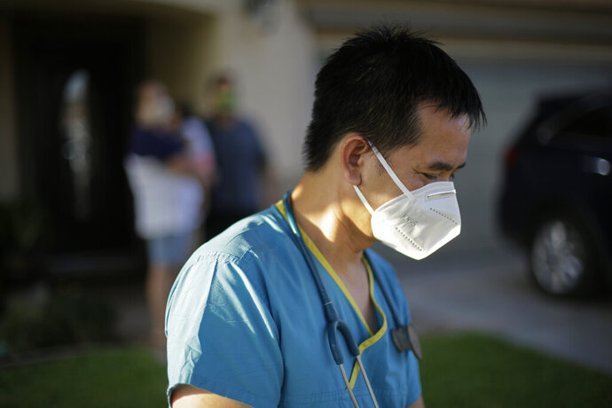 Dr. Tien Vo goes to leave after talking with a family quarantining after they tested positive for the coronavirus Thursday, July 23, 2020, in Calexico, Calif. Vo and members of his clinic bring food to patients that test positive and agree to quarantine. (AP Photo/Gregory Bull)