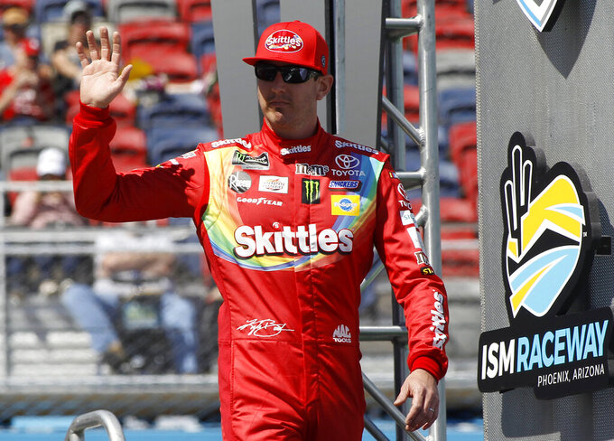 Kyle Busch waves to the crowd during driver introductions prior to the start of the NASCAR Cup Series auto race at ISM Raceway, Sunday, March 10, 2019, in Avondale, Ariz. (AP Photo/Ralph Freso)