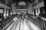 FILE - In this 1924 file photo, immigrants from Europe sit in the registry room at Ellis Island in New York harbor. Throughout history, the United States has used all sorts of physical or mental exams for immigrants seeking just to get into the country outside of becoming a citizen. (AP Photo/File)
