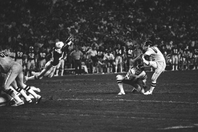 FILE - In this Jan. 2, 1982, file photo, San Diego Chargers' Rolf Benirschke (6), right, kicks the game-winning field goal in overtime of an NFL football AFC playoff game, against the Miami Dolphins, in Miami, Fla.  Ed Luther holds the ball. The Chargers won 41-38. Decades later, Rolf Benirschke still gets emotional talking about his second chances. (AP Photo/File)