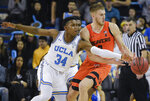 UCLA guard David Singleton, left, swipes the ball away from Oregon State forward Tres Tinkle during the second half of an NCAA college basketball game in Los Angeles, Thursday, Feb. 21, 2019. UCLA won 68-67. (AP Photo/Kelvin Kuo)