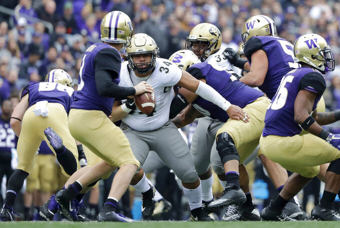 Washington quarterback Jake Browning, left, is pressured by Colorado defensive lineman Mustafa Johnson during the first half of an NCAA college football game, Saturday, Oct. 20, 2018, in Seattle. (AP Photo/Ted S. Warren)