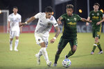 LA Galaxy forward Cristian Pavon (10) controls the ball in front of Portland Timbers forward Andy Polo (7) during the second half of an MLS soccer match Monday, July 13, 2020, in Kissimmee, Fla. (AP Photo/Phelan M. Ebenhack)