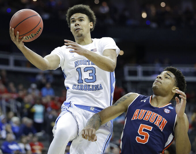 North Carolina's Cameron Johnson (13) heads to the basket past Auburn's Chuma Okeke (5) during the first half of a men's NCAA tournament college basketball Midwest Regional semifinal game Friday, March 29, 2019, in Kansas City, Mo. (AP Photo/Charlie Riedel)
