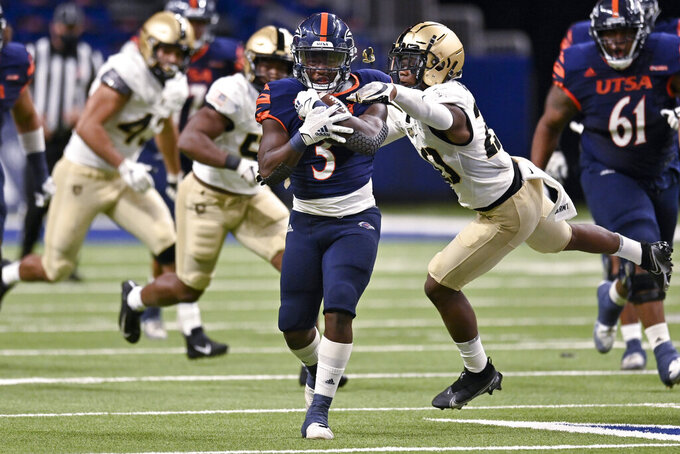 UTSA's Sincere McCormick (3) evades Army's Marquel Broughton during an NCAA college football game on Saturday, Oct. 17, 2020, in San Antonio, Texas. (AP Photo/Darren Abate)