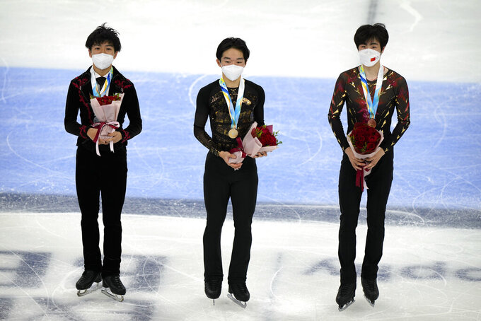 From left, men's singles silver medalist Shun Sato of Japan, gold medalist Yuma Kagiyama of Japan, and bronze medalist Jin Boyang of China pose on the ice during their medal ceremony at the Asian Open Figure Skating Trophy, a test event for the 2022 Winter Olympics, at the Capital Indoor Stadium in Beijing, Friday, Oct. 15, 2021. (AP Photo/Mark Schiefelbein)