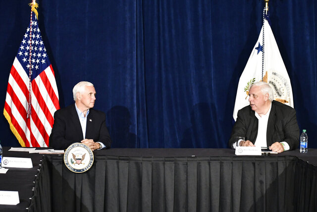 In this photo made available by the West Virginia's governor's office, Vice President Mike Pence, left, meets with Gov. Jim Justice at Justice's resort, The Greenbrier, in White Sulphur Springs, W.Va., to discuss the coronavirus and a fundraiser for the Trump-Pence campaign. (Office of the Governor via AP)
