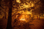 FILE - In this Nov. 9, 2018, file photo, firefighters work to keep flames from spreading through the Shadowbrook apartment complex as a wildfire burns through Paradise, Calif. Pacific Gas and Electric says it has reached a $13.5 billion settlement that will resolve all major claims related to devastating wildfires blamed on its outdated equipment and negligence. The settlement, which the utility says was reached Friday, Dec. 6, 2019, still requires court approval. (AP Photo/Noah Berger, File)