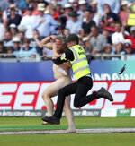 A security officer jumps to restrain a streaker who ran into the field during the Cricket World Cup match between New Zealand and England in Chester-le-Street, England, Wednesday, July 3, 2019. Security appeared very slow to react as the spectator jogged toward the wicket and danced about in front of New Zealand batsmen Tom Latham and Mitchell Santner. He then weaved around security staff as they attempted to stop him before he was brought to the ground. (AP Photo/Scott Heppell)