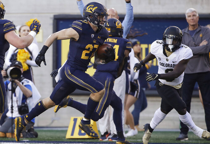 "FILE - In this Nov. 24, 2018, file photo, California safety Ashtyn Davis (27) runs past Colorado wide receiver K.D. Nixon, right, as he returns an interception for a touchdown during the first half of an NCAA college football game in Berkeley, Calif. Cal, which plays Stanford on Saturday, has held its last five opponents to 21 points or less and the defense forced five turnovers and scored two TDs in last week's win over Colorado. ""I feel like every guy on the defense, every position group has a good understanding of the defense and where the fit,"" said Davis, who had two interceptions and a touchdown last week. ""It's made us much better in every aspect of the game.""  (AP Photo/Jeff Chiu, File)"