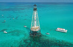 This aerial photo provided by the Florida Keys News Bureau shows boats with snorkelers anchored around Alligator Reef Lighthouse, Tuesday, Sept. 7, 2021, off Islamorada, Fla., in the Florida Keys. On Tuesday, officials from the Islamorada-based Friends of the Pool, Inc., announced that U.S. Secretary of the Interior Deb Haaland approved a recommendation from the National Park Service that the organization be granted ownership of the lighthouse under the National Historic Lighthouse Preservation Act. Friends of the Pool hopes to raise about $9 million to preserve the almost 150-year-old structure. (Andy Newman/Florida Keys News Bureau via AP)