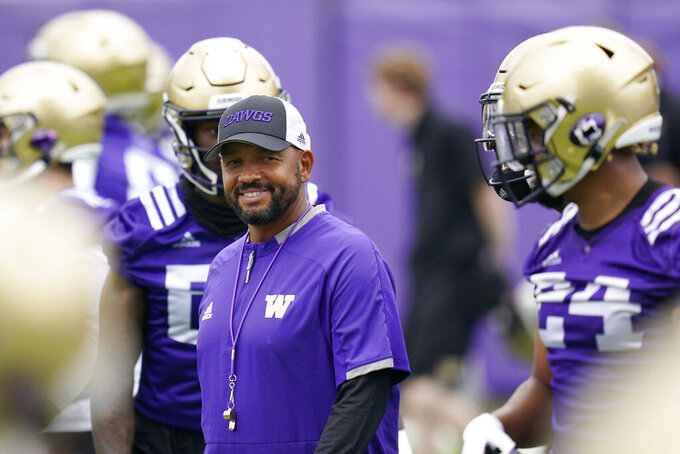 FILE - Washington head coach Jimmy Lake stands with players during NCAA college football practice in Seattle, in this Friday, Aug. 6, 2021, file photo. Washington begins the 2021 season as one of the favorites in the Pac-12 North Division, while also trying to erase the bad taste of how last year ended when a COVID-19 outbreak brought a sudden end to an already truncated schedule. (AP Photo/Elaine Thompson, File)