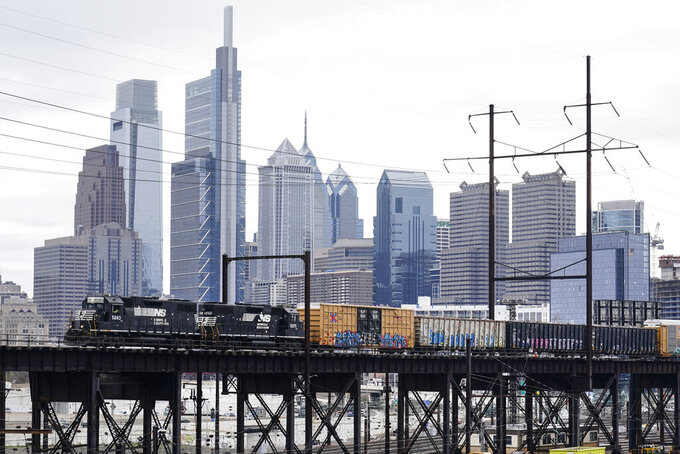 FILE - In this March 31, 2021 file photo, a Norfolk Southern freight train moves along elevated tracks in Philadelphia. Norfolk Southern's profit improved in the first quarter as the railroad hauled 3% more freight while the economy continued to recover from thee coronavirus pandemic. The railroad said Wednesday, April 28 that it earned $673 million, or $2.66 per share, during the quarter. (AP Photo/Matt Rourke, File)