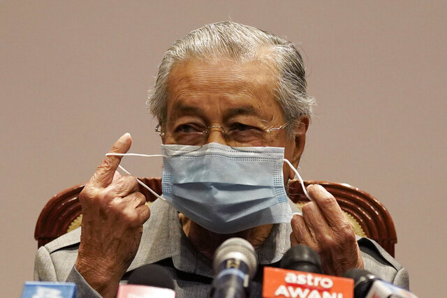 Malaysia former Prime Minister Mahathir Mohamad removes his face mask before a press conference at his office of Perdana Foundation in Putrajaya, Malaysia, Monday, May 18, 2020. Mahathir slammed the government for using the pandemic as an excuse to block parliament from sitting. The king in his speech urged lawmakers not to stir up another political crisis but to focus on the people's welfare amid the virus outbreak. (AP Photo/Vincent Thian)