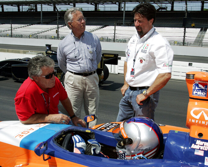 FILE - In this May 26, 2005, file photo, Infiniti Pro Series driver Marco Andretti, bottom, talks to his grandfather and 1969 Indy 500 champion Mario Andretti, left, uncle Aldo Andretti, top center, and father Michael Andretti during practice for the Futaba Freedom 100 auto race at Indianapolis Motor Speedway in Indianapolis. Mario feels the same pain as so many others these days. His wife died two years ago, long before the pandemic. And his beloved nephew lost a brutal battle with colon cancer. But then COVID-19 claimed his twin brother Aldo and one of the greatest racers of all time is not immune from the loneliness and depression sweeping the world. (AP Photo/Michael Conroy, File)