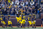 Michigan linebacker Junior Colson (25) celebrates his recovery of a Rutgers fumble with teammates in the fourth quarter of an NCAA college football game in Ann Arbor, Mich., Saturday, Sept. 25, 2021.  (AP Photo/Tony Ding)