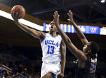 UCLA guard Kris Wilkes, left, goes to the basket while defended by Washington forward Noah Dickerson during the second half of an NCAA college basketball game in Los Angeles, Sunday, Dec. 31, 2017. UCLA won 74-53. (AP Photo/Ringo H.W. Chiu)