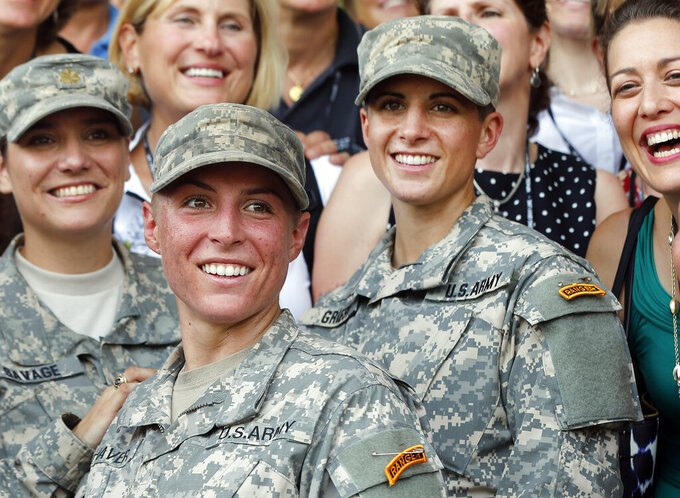 FILE - In this Aug. 21, 2015, file photo, Army 1st Lt. Shaye Haver, center, and Capt. Kristen Griest, right, pose for photos with other female West Point alumni after an Army Ranger school graduation ceremony at Fort Benning, Ga. Haver and Griest became the first female graduates of the Army's rigorous Ranger School. (AP Photo/John Bazemore, File)