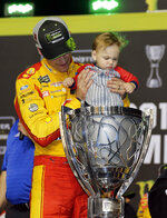 Joey Logano holds his son Hudson in the trophy after winning the NASCAR Cup Series championship auto race at Homestead-Miami Speedway, Sunday, Nov. 18, 2018, in Homestead, Fla. (AP Photo/Terry Renna)