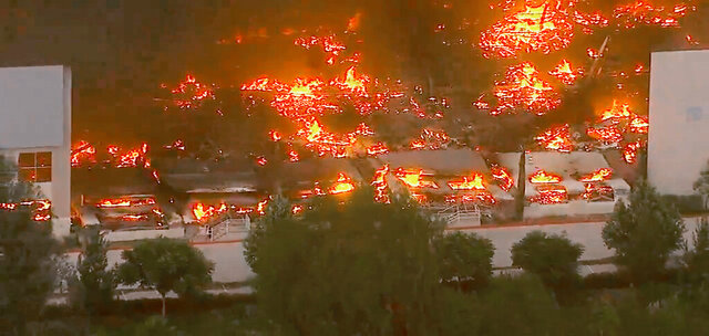 This photo taken from video provided by KABC-TV shows a raging fire destroying a huge commercial building Friday, June 5, 2020 in Redlands, Calif., about 60 miles (96 kilometers) east of Los Angeles. The fire early Friday destroyed a Southern California distribution facility that was used to ship items to Amazon customers but authorities said employees got out and there were no reports of injuries. A half-dozen fire departments were unable to stop flames from destroying the sprawling structure. (KABC-TV via AP)