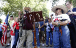 Steven Willeford, holds up a rifle as he and Dr. Alma Arredondo-Lynch, right, holds a pistol as gun rights advocates gather outside the Texas Capitol where Texas Gov. Greg Abbott held a round table discussion, Thursday, Aug. 22, 2019, in Austin, Texas. Abbott is meeting in Austin with officials from Google, Twitter and Facebook as well as officials from the FBI and state lawmakers to discuss ways of combatting extremism in light of the recent mass shooting in El Paso that reportedly targeted Mexicans. (AP Photo/Eric Gay)