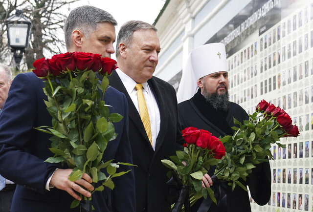 U.S. Secretary of State Mike Pompeo, center, Ukrainian Foreign Minister Vadym Prystaiko, left, and Metropolitan Epifaniy, head of the Orthodox Church of Ukraine, take part in a ceremony at the memorial to Ukrainian soldiers, who were killed in a recent conflict in the country's eastern regions, in Kyiv, Ukraine, Friday Jan. 31, 2020. U.S. Secretary of State Mike Pompeo opened a visit to Ukraine on Friday facing a delicate balancing act as he tries to boost ties with a critical ally at the heart of the impeachment trial while not providing fodder for Democrats seeking to oust President Donald Trump. (Kevin Lamarque/Pool via AP)