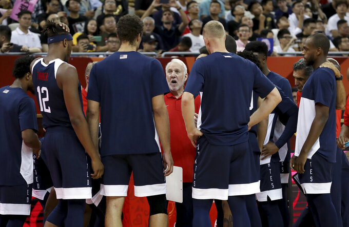 FILE - In this Sept. 1, 2019, file photo, U.S. coach Gregg Popovich talks to players before a Group E match against the Czech Republic in the FIBA Basketball World Cup in Shanghai. Popovich, coach of the San Antonio Spurs, knows that the NBA schedule and how it comes very close to the start of the rescheduled Tokyo Games will be a challenge for USA Basketball to navigate next year when choosing the 12 players who will try to win a fourth consecutive men's Olympic gold medal. Popovich will be head coach of the Olympic team for the first time. (AP Photo/Ng Han Guan, File)