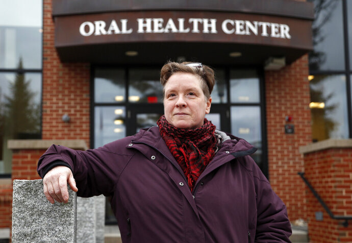 In this Wednesday, April 24, 2019 photo, Ebyn Moss poses for a photo outside the University of New England's dental school in Portland, Maine. Moss has made the two-hour drive several times from her home in Troy, Maine, for extensive treatment at the dental school after breaking a tooth below the gum line in 2017. She said a dental therapist nearby her home would have made preventive care easier in the first place. Several states have recently pass laws authorizing dental therapists, which perform basic procedures and leave the more complex work to dentists. (AP Photo/Robert F. Bukaty)