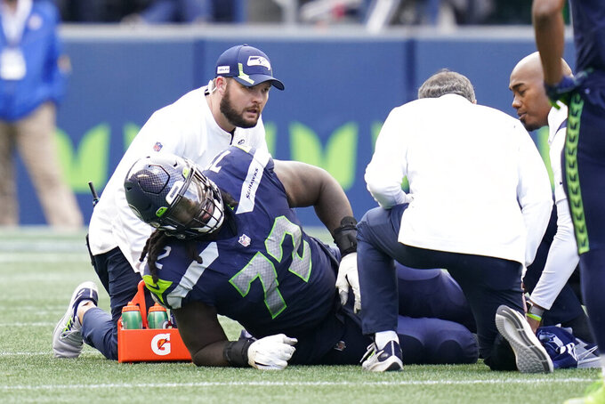 Seattle Seahawks offensive tackle Brandon Shell is looked at by trainers after an injury during the second half of an NFL football game against the Tennessee Titans, Sunday, Sept. 19, 2021, in Seattle. The Titans won 33-30 in overtime. (AP Photo/Elaine Thompson)