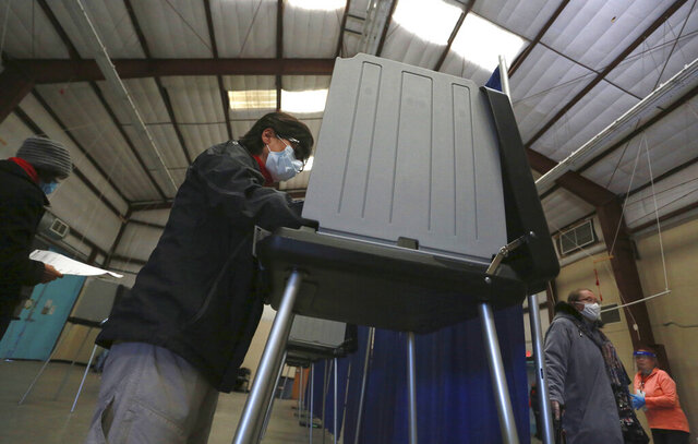 Sandy Martinez begins filling in the first in-person ballot of the day at an early voting center on Saturday, Oct. 17, 2020, in Santa Fe, N.M. Early voting centers opened Saturday across the state. In-person early voting extends for two weeks through Oct. 31. (AP Photo/Cedar Attanasio)