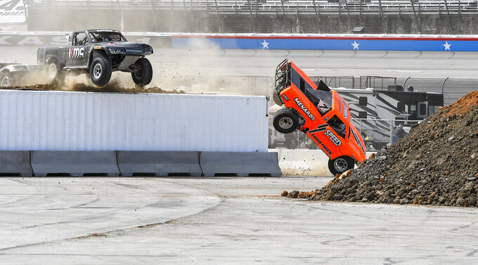 Robby Gordon, right, drives off the edge of a ramp as Jeff Hoffman, left, makes the jump attempt during the Outdoor Powersports Offroad Rumble SST Race prior to a NASCAR Cup auto race at Texas Motor Speedway, Sunday, March 31, 2019, in Fort Worth, Texas. (AP Photo/Larry Papke)