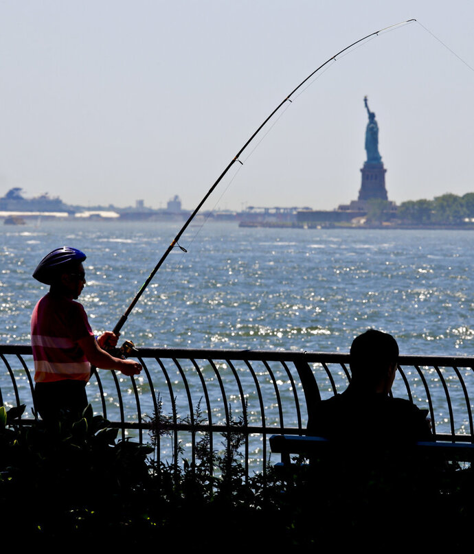 FI LE - In this June 17, 2018, file photo, man fishes from the Battery City Park esplanade as temperature edge near 90 degrees in New York. The weather in New York City in a few decades will feel like how Arkansas is now. Chicago will seem like Kansas City and San Francisco will get a Southern California climate if global warming pollution continues at the current pace, a new study finds. (AP Photo/Bebeto Matthews, File)