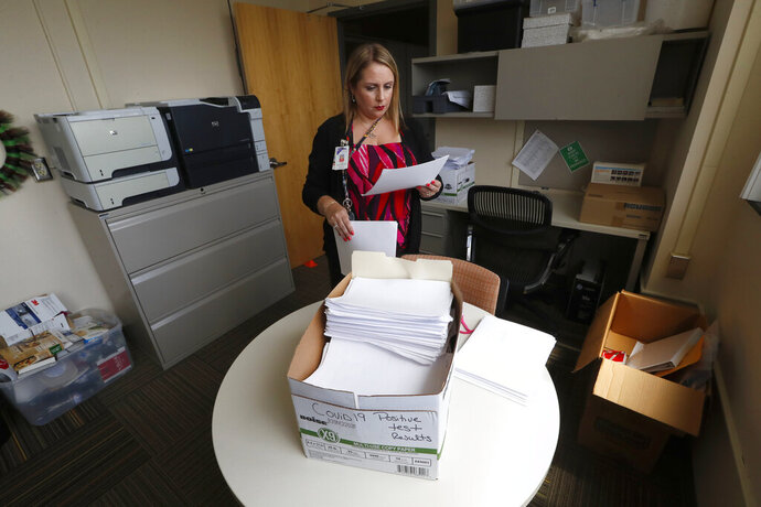 Jennifer Gottschalk, environmental health supervisor of the Toledo-Lucas County Health Department, reads paperwork about positive COVID-19 test results in Toledo, Ohio, on Wednesday, June 24, 2020. (AP Photo/Paul Sancya)