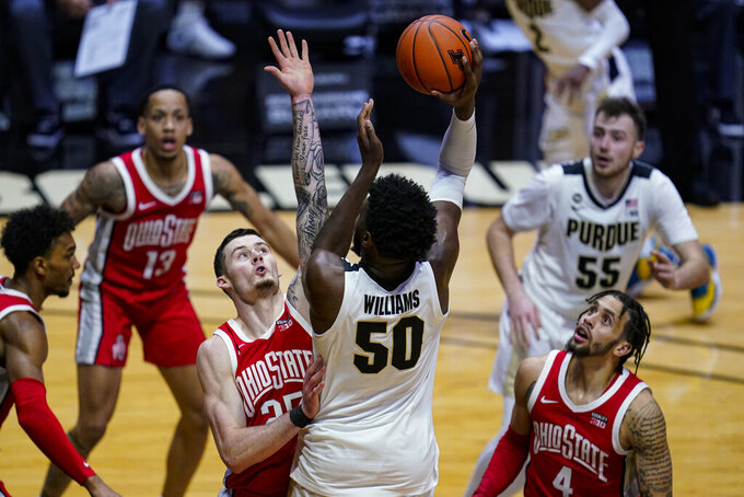 Purdue forward Trevion Williams (50) shoots over Ohio State forward Kyle Young (25) during the second half of an NCAA college basketball game in West Lafayette, Ind., Wednesday, Dec. 16, 2020. (AP Photo/Michael Conroy)