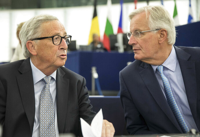 European Commission president Jean-Claude Juncker, left, speaks whith European Union chief Brexit negotiator Michel Barnier Wednesday, Sept. 18, 2019 at the European Parliament in Strasbourg, eastern France. The risk of Britain leaving the European Union without a divorce deal remains