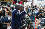 Quincy Mason, son of George Floyd, listens Wednesday, June 3, 2020 as family attorney Ben Crump, left, addresses a news conference as they and some Floyd family members visit the site in Minneapolis. Floyd, a black man died after being restrained by Minneapolis police officers on May 25 .(AP Photo/Jim Mone)