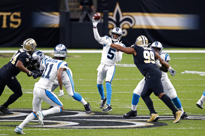 Carolina Panthers quarterback Teddy Bridgewater (5) passes under pressure from New Orleans Saints defensive tackle Shy Tuttle (99) and defensive end Cameron Jordan (94) in the first half of an NFL football game in New Orleans, Sunday, Oct. 25, 2020. (AP Photo/Butch Dill)