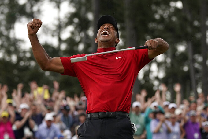 File-This April 14, 2019, file photo shows Tiger Woods reacting as he wins the Masters golf tournament in Augusta, Ga. Woods stands tall in the Georgia pines. Hugs and chants and exultation, Masters crown, a restoration. (AP Photo/David J. Phillip,File)