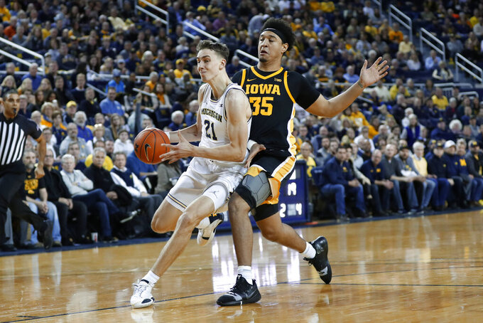 Michigan guard Franz Wagner (21) drives against Iowa forward Cordell Pemsl (35) in the first half of an NCAA college basketball game in Ann Arbor, Mich., Friday, Dec. 6, 2019. (AP Photo/Paul Sancya)