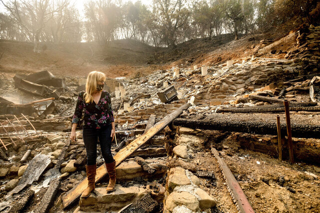 Pam, who declined to give a last name, examines the remains of her partner's Vacaville, Calif., home on Friday, Aug. 21, 2020. The residence burned as the LNU Lightning Complex fires ripped through the area Tuesday night. (AP Photo/Noah Berger)