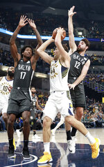 Indiana Pacers forward Bojan Bogdanovic (44) gets to the basket defended by Brooklyn Nets center Ed Davis (17) and Brooklyn guard Joe Harris in the first half of an NBA basketball game, Saturday, Oct. 20, 2018, in Indianapolis. (AP Photo/R Brent Smith)