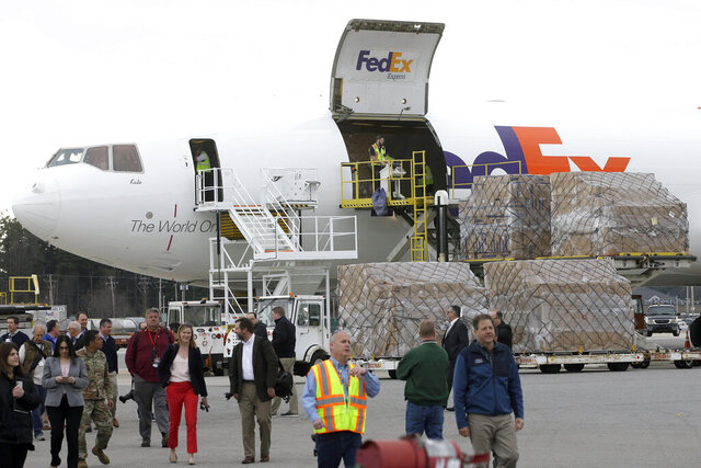 Law enforcement and government officials, along with members of the media, walk along the tarmac as pallets containing personal protective equipment, right, are unloaded from a FedEx cargo plane, Sunday, April 12, 2020, at Manchester-Boston Regional Airport, in Manchester, N.H. The cargo plane, carrying about 91,000 pounds of personal protective equipment, which is helpful in preventing the spread of the coronavirus, arrived at the airport in Manchester from Shanghai, China, after passing through U.S. Customs in Anchorage, Alaska early Sunday, April 12.(AP Photo/Steven Senne)