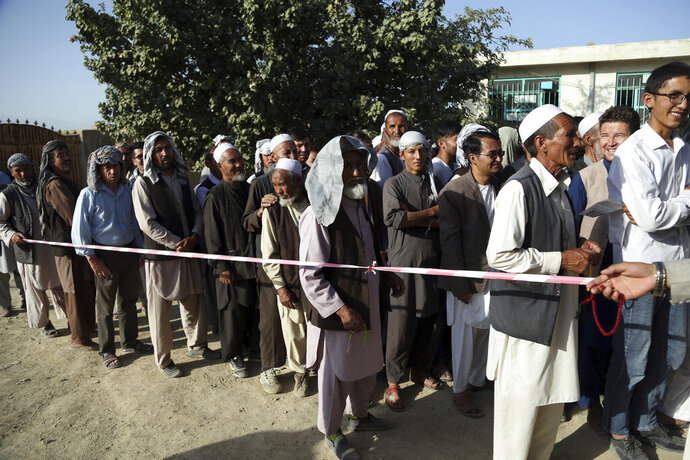 Men line up outside a polling station in western neighborhood of Kabul, Afghanistan, Saturday, Sept. 28, 2019. Afghans headed to the polls on Saturday to elect a new president amid high security and threats of violence from Taliban militants, who warned citizens to stay away from polling stations or risk being hurt. (AP Photo/Rahmat Gul)