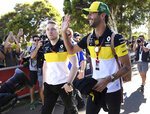 Renault driver Daniel Ricciardo of Australia, center right, waves to fans as he arrives at the track for the Australian Formula One Grand Prix in Melbourne, Thursday, March 12, 2020. (AP Photo/Andy Brownbill)