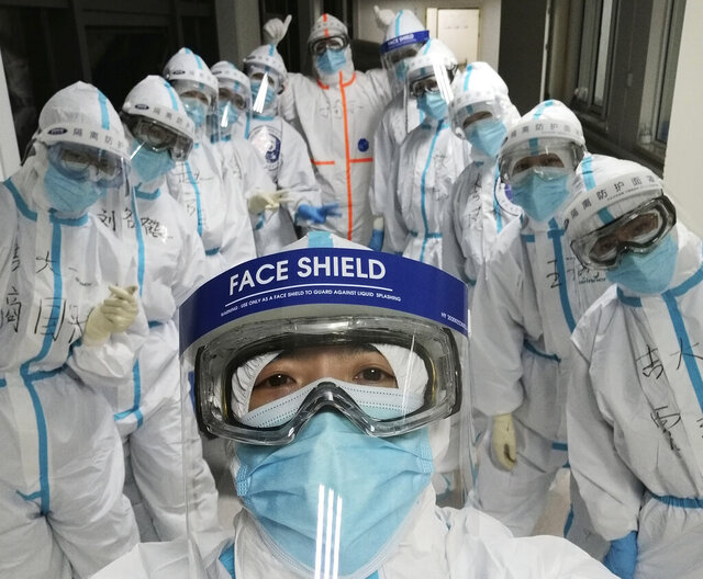 In this photo taken and released by Chinese nurse Zhang Dan, she poses for a photo with colleagues at the Wuhan Pulmonary Hospital in Wuhan in central China's Hubei province, Friday, April 4, 2020. Zhang was among the first to respond to the call for help in China's coronavirus epicenter. The 36-year-old nurse worked through grueling days, ministering to patients who needed assistance from breathing to merely eating. She struggled — but then, a little street dog helped her through. (Zhang Dan via AP)
