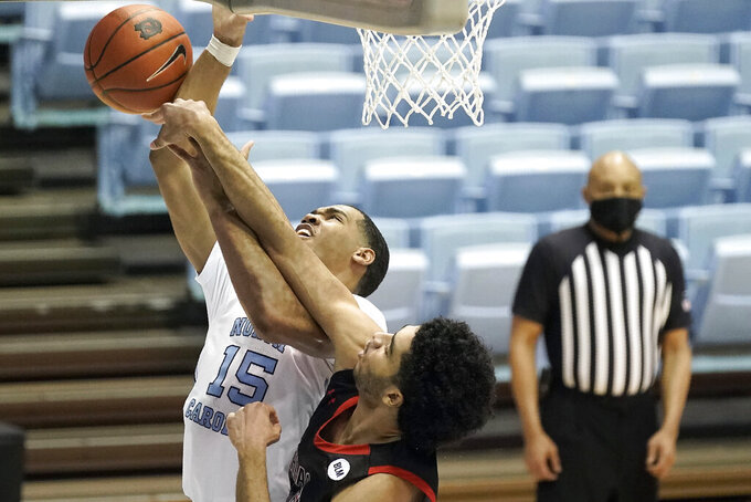 North Carolina forward Garrison Brooks (15) drives to the basket while Northeastern forward Jason Strong blocks during the first half of an NCAA college basketball game in Chapel Hill, N.C., Wednesday, Feb. 17, 2021. (AP Photo/Gerry Broome)